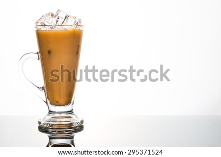 Refreshing ice cold coffee with milk in transparent latte glass flushed left