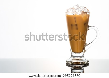 Refreshing ice cold coffee with milk in transparent latte glass flushed right