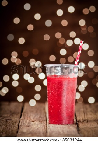 Refreshing ice cold glass of ripe red strawberry smoothie blended with low fat yoghurt for a healthy summer drink against a twinkling bokeh of party lights in the darkness - stock photo
