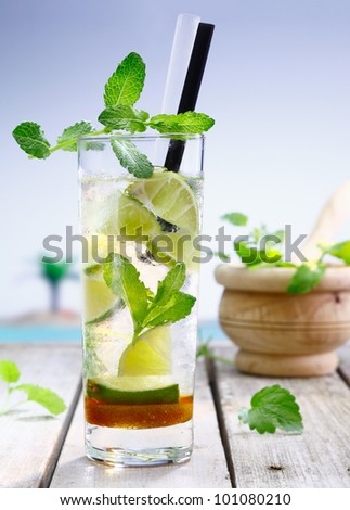 Refreshing lemon or lime cocktail served cold in a tall glass with vodka or gin and garnished with mint, perfect for that summer vacation - stock photo