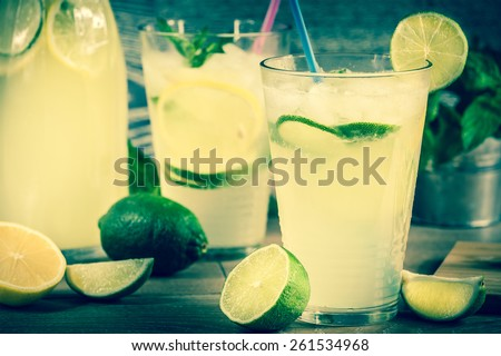 Refreshing lemonade drink and ripe fruits against wooden background - stock photo