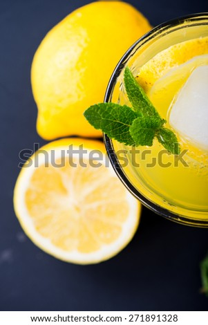 Refreshing lemonade with fresh citrus , mint and ice in glass on black background