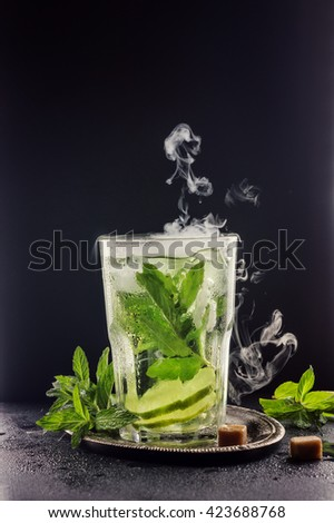 refreshing lemonade with mint and lime in a transparent glass on a dark background. dry ice, a beautiful effect, patterns. - stock photo