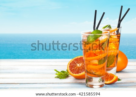 Refreshing lemonade with oranges and mint on wooden table. - stock photo