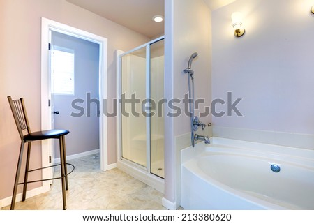 Refreshing light lavender bathroom with white bath tub, glass door shower and chair - stock photo