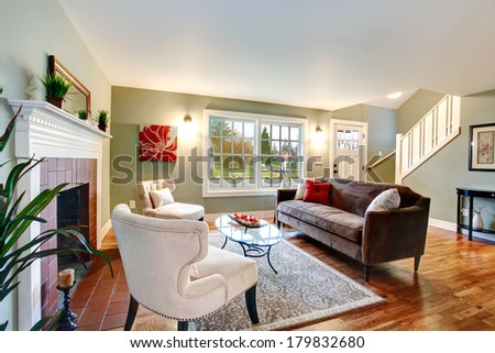 Refreshing living room with light green walls, hardwood floor and white ceiling. Furnished with brown sofa, chairs and glass coffee table. - stock photo