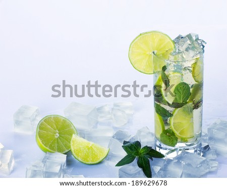 refreshing  mojito and many cubes of ice on table with water drop on light blue background