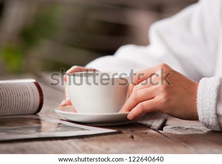 Refreshing morning tea. Woman hands with cup and magazine - stock photo