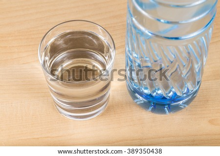 Refreshing natural mineral water in plastic bottle with transparent glass - stock photo