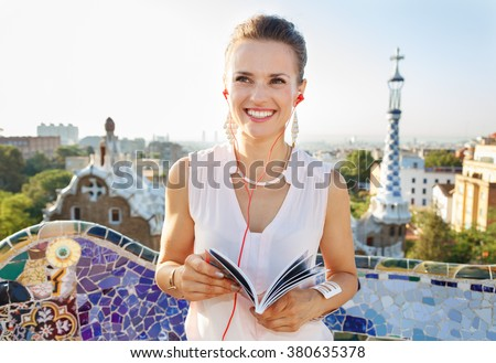 Refreshing promenade in unique Park Guell style in Barcelona, Spain. Happy young woman holding tourist guide and listening audioguide while in Park Guell, Barcelona, Spain - stock photo