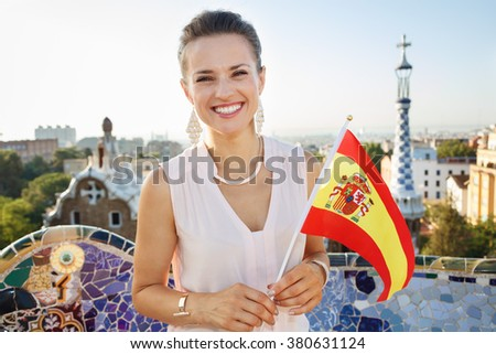 Refreshing promenade in unique Park Guell style in Barcelona, Spain. Portrait of smiling young woman tourist with Spain flag in Park Guell, Barcelona, Spain