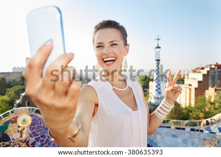 Refreshing promenade in unique Park Guell style in Barcelona, Spain. Portrait of smiling young woman showing victory gesture and taking selfie with smartphone while in Park Guell, Barcelona, Spain