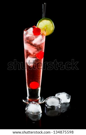 refreshing red cocktail with sparkling water and ice garnished with a lime and cherry - stock photo