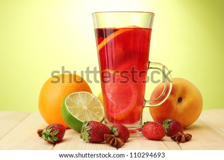 Refreshing sangria in glass with fruits, on wooden table, on green background