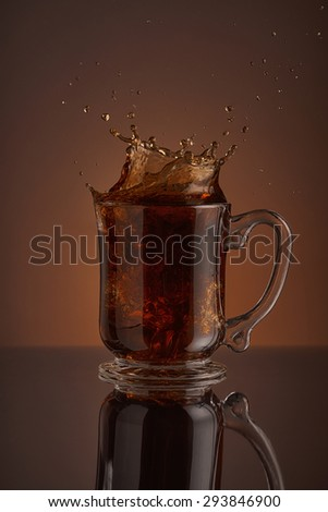 Refreshing splash of black ice coffee drink on a brown background. Liquid drink pouring into a cup with ice. Pour high speed beverage for promoting restaurant, bistro and bar. Close-up design liquor