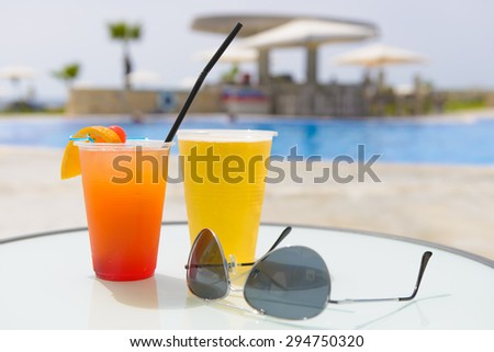 Refreshing summer cocktails and a pair of sunglasses on a table beside a swimming pool at a vacation resort. - stock photo