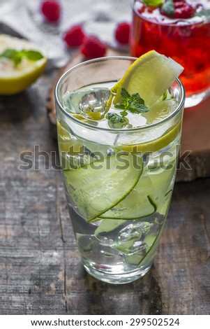 Refreshing summer cocktails - Gin and Tonic with Cucumber and Raspberry Crush in the background - stock photo