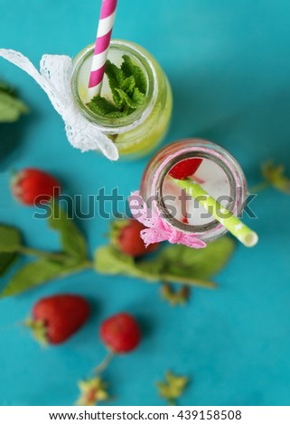 Refreshing summer drink with juicy fruit and fresh mint in a vintage glass bottles closeup. Top view. - stock photo