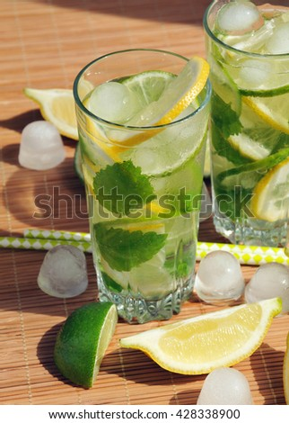 Refreshing summer drink with lemon, lime, mint and ice in glasses - stock photo