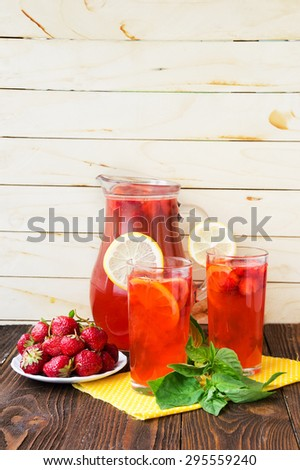 Refreshing summer drink with strawberry and basil in jug and glasses on the wooden table - stock photo