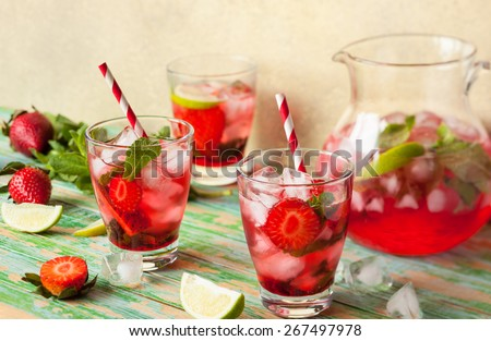 Refreshing summer drink with Strawberry in jug and glasses on the vintage wooden table - stock photo