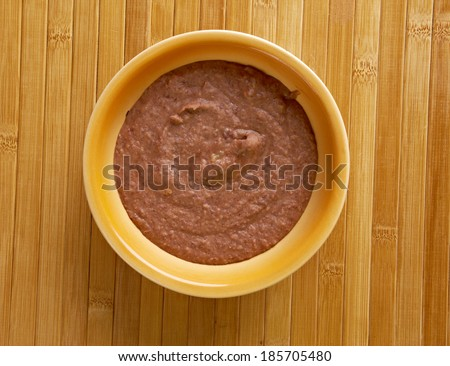 Refried beans dish of cooked and mashed beans and is a traditional staple of Mexican and Tex-Mex cuisine - stock photo