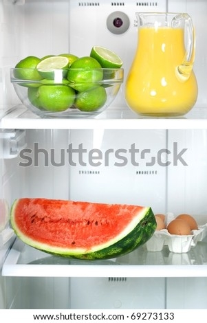 Refrigerator full with some kinds of food - fruits, juice and eggs - stock photo