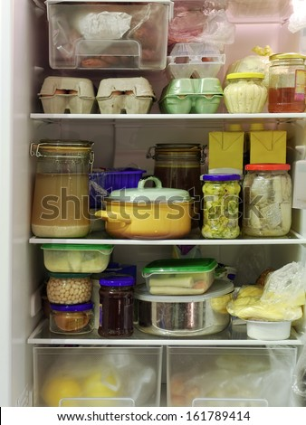 Refrigerator inside full of assorted food ingredients, fruit, vegetables, meat and dairy products - stock photo