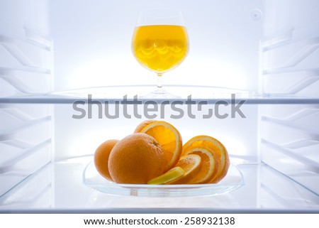 Refrigerator,  modern stylish design. Interior, inside  image, glass shelf, oranges, cocktail, jelly bean, clean, light, web banner - stock photo