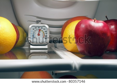 Refrigerator thermometer inside the top shelf of a cool food storage fridge to make sure perishables are kept safe and cold enough. - stock photo