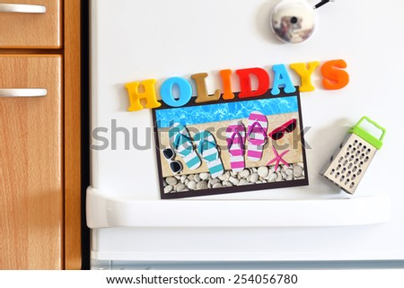 Refrigerators door with colorful text Holidays and Photo By The Pool - stock photo