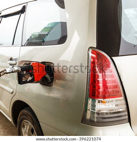 Refuel gasoline to car by red nozzle pump - stock photo