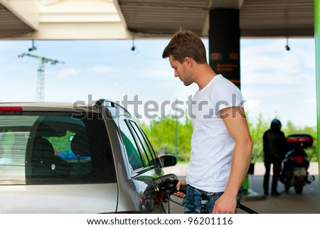Refuel the car on a gas station; man holding the tap - stock photo