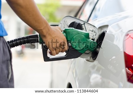 Refueling Car With Gasoline Pump Nozzle, Selective Focus on pump nozzle - stock photo