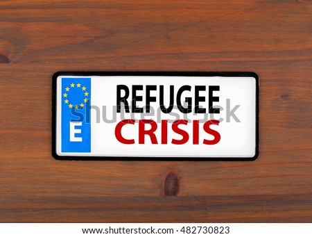 Refugee Crisis. On a wooden board metal plate with european union flag