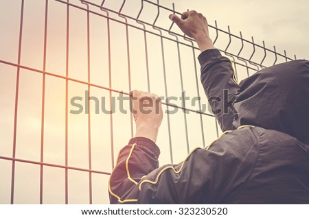 Refugee men and metal fence. Refugee crisis concept. - stock photo