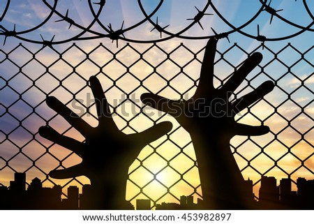 Refugees concept. Silhouette refugee hands near the barbed wire fence and cityscape