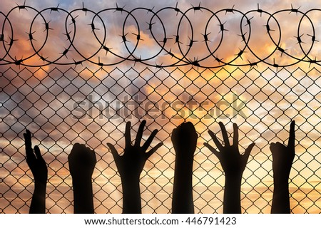 Refugees hands silhouette near the fence of barbed wire. refugee concept