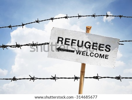 refugees welcome sign and barbwire background