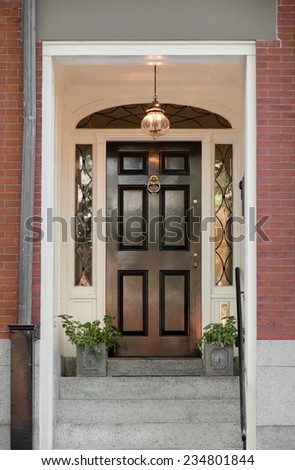 Regal Black Front Door with Lunette Under White Portico - stock photo