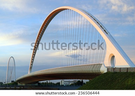 REGGIO EMILIA ,ITALY -  30 JULY 2014:  perspective of the bridge that crosses the highway on a cloudy day. the bridge is designed by 'architect Calatrava and is the symbol of the city