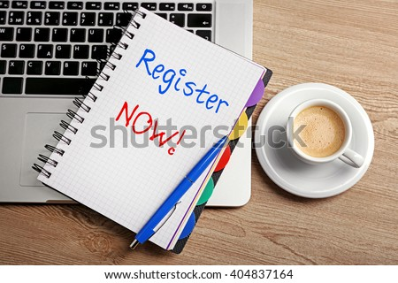 Register now written in notebook, laptop and cup of coffee on table, top view - stock photo