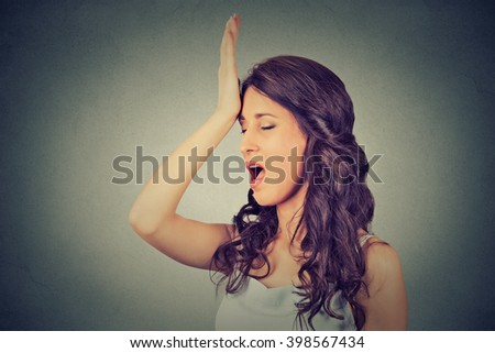 Regrets wrong doing. Closeup portrait silly young woman, slapping hand on head having duh moment isolated on gray background. Negative human emotion facial expression feeling, body language, reaction - stock photo
