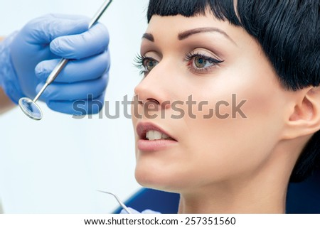 Regular health check. Dentist makes the process of treatment of a beautiful young girl. - stock photo