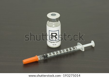 Regular insulin vial with insulin syringe. - stock photo