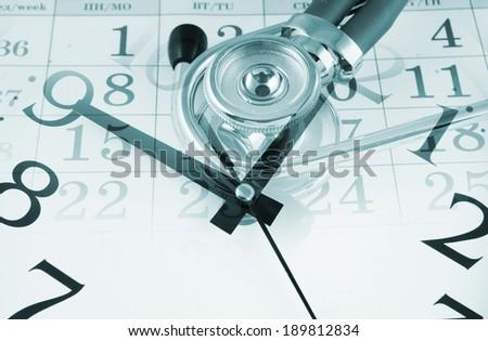 Regular medical examination concept, stethoscope on calendar and clock - stock photo
