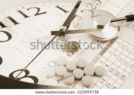 Regular medical examination concept, stethoscope on calendar, drugs and clock  - stock photo
