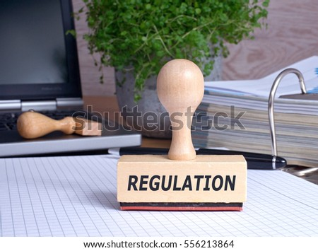Regulation Stamp in the Office with binder and laptop in the background