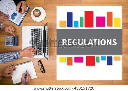 REGULATIONS Business team hands at work with financial reports and a laptop - stock photo