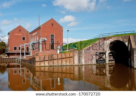 Regulatory sluice by a sea wall and pump house